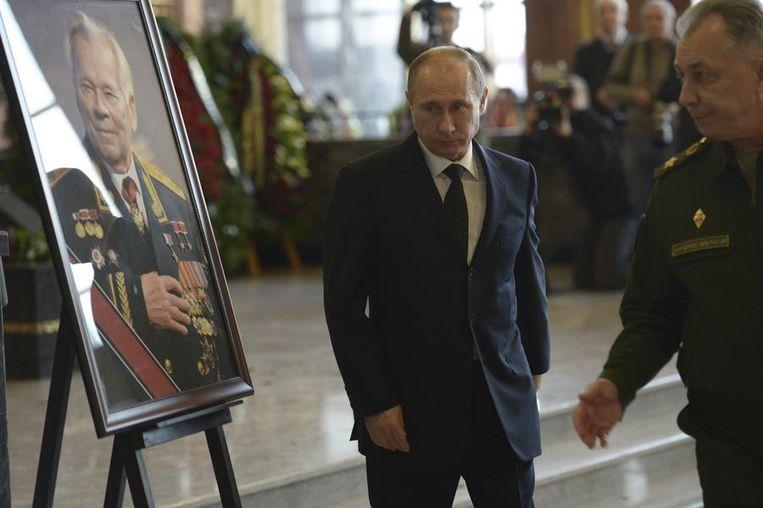 Russische president Vladimir Poetin loopt langs een foto van Michail Kalasjnikov om zijn laatste eer te bewijzen. Beeld reuters