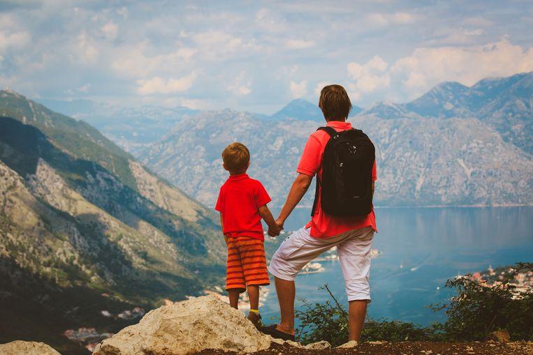 Vader en kind samen in de bergen. Beeld ThinkStock