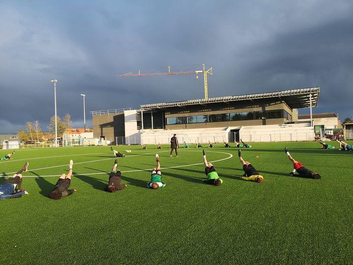 Een training van KFC Moerbeke met op de achtergrond de nieuwe sporthal en toekomstige kantine waarvan de bouw nu is stilgelegd.
