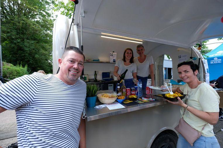 Philippe Leemans bij zijn nieuwe foodtruck. Achter de toog staan zijn vrouw en dochter, zij bedienen een klant.