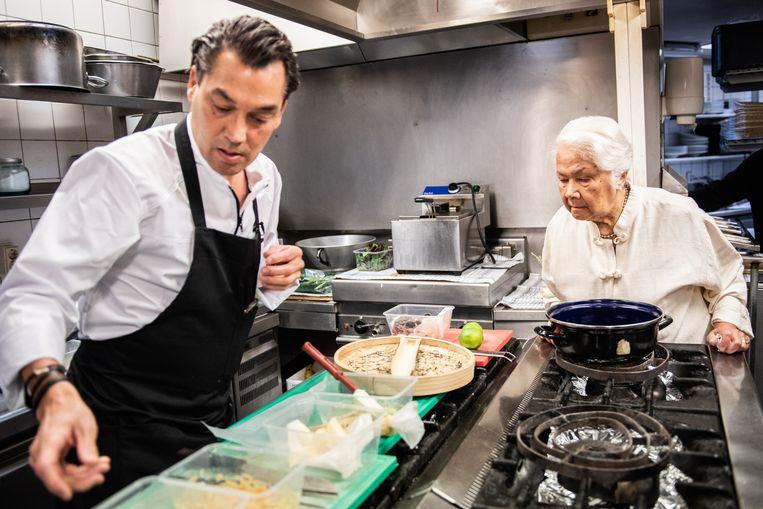 Chef Pascal Jalhay bereidt Indisch gerecht op moderne manier. Anita Boerenkamp kijkt aandachtig toe.  Beeld Simon Lenskens