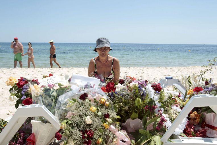 Een toerist legt bloemen neer op het strand van het Imperial Marhabahotel, waar 39 buitenlanders werden doodgeschoten. Beeld REUTERS