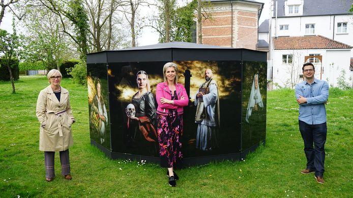 Christa Maes, Inge Brocken en Bert Verwerft aan de Vijfkiosk met daarop schilderachtige foto's van Beverse nakomelingen van Vijd, afgebeeld in middeleeuwse outfit.