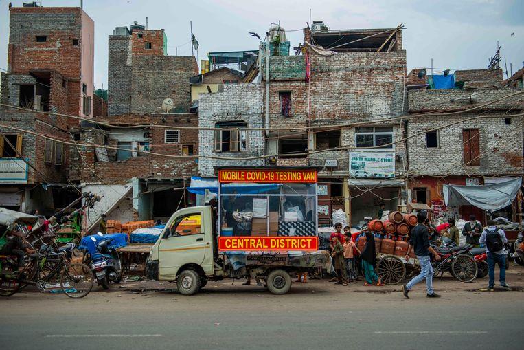 Een mobiel laboratorium voor het testen op Covid-19 staat geparkeerd in een sloppenwijk in de Indiase miljoenenhoofdstad Delhi.  Beeld Hollandse Hoogte / Zuma Press