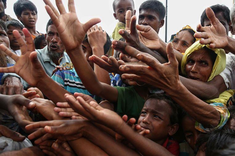 Vluchtelingen reiken om eten in een vluchtelingenkamp aan de grens tussen Myanmar en Bangladesh. Beeld afp
