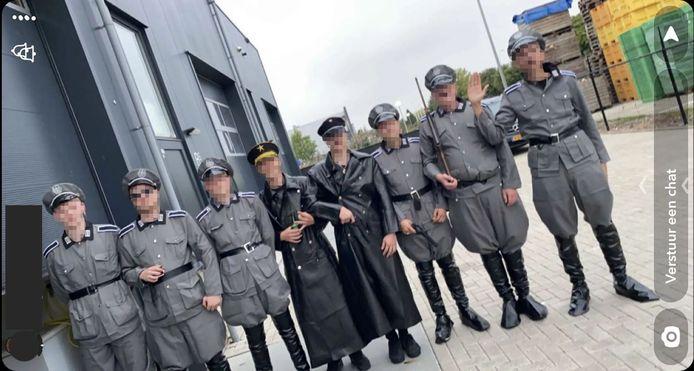 Urker jongeren in nazi-legerkledij poseren voor een foto op het industrieterrein van Urk