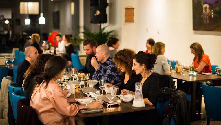 Hun restaurant zit op een tochtige hoek en oogt met z'n felle licht, knalblauwe stoelen en posters van bezienswaardigheden een beetje als een ouderwets reisbureau Beeld Mats van Soolingen