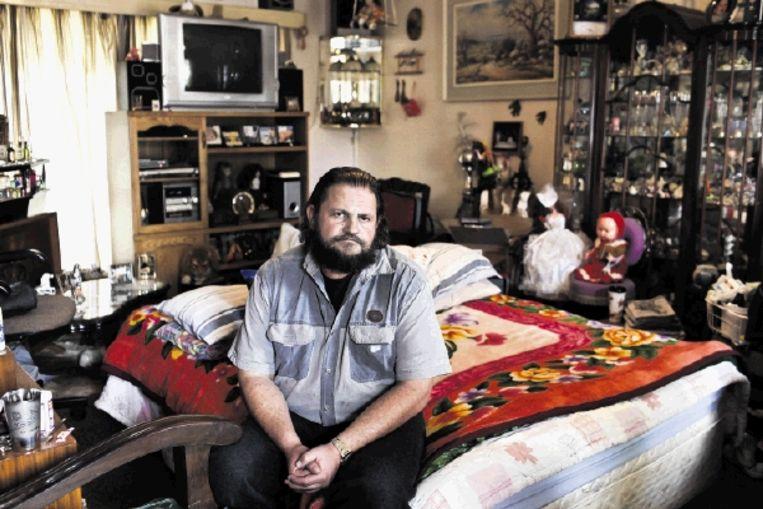 Ben van Niekerk en zijn echtgenote Christel zijn ingetrokken bij Christels ouders. Hun bed staat al maanden in de kleine propvolle woonkamer. (Trouw) Beeld