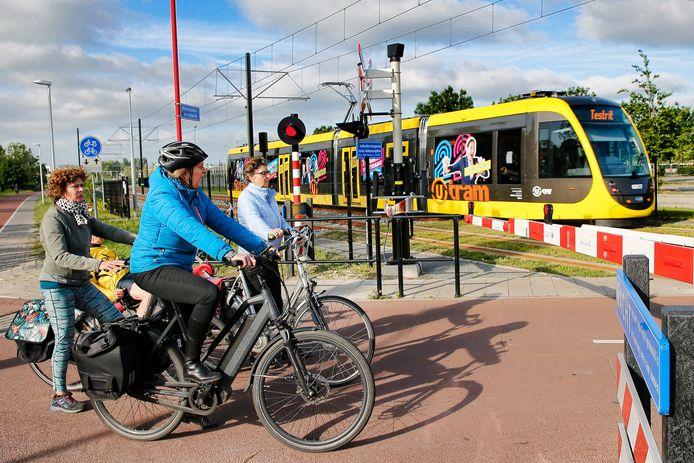 Fietsers wachten bij spoorbomen op de Koningsweg voor een tram, die een testrit doet op het traject van de Uithoflijn.