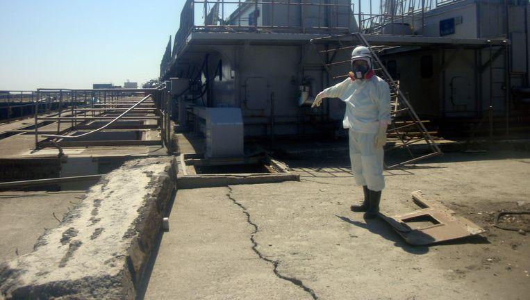 Eén van de techneuten van Fukushima 1 wijst op een net ontdekte scheur bij de kerncentrale. Beeld AP