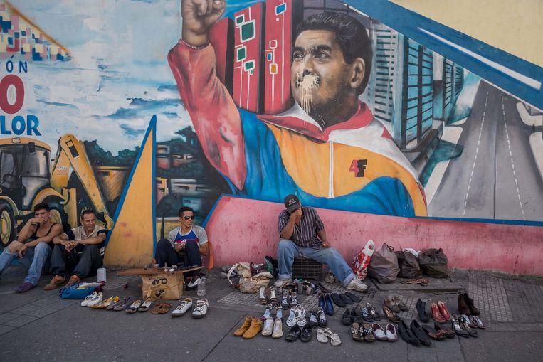 Schoenverkopers in de straten van Caracas, voor een muurschildering van president Nicolás Maduro.  Beeld EPA