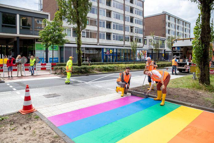 Wethouder Peter de Haan, voorzitter van Shout Kees van Asselt en burgemeester Floor Vermeulen (van links naar rechts) leggen de laatste hand aan de regenboogoversteekplaats aan de Stadsbrink.