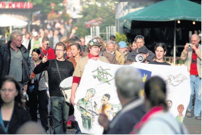 De demonstratie van het platform Veenendalers Voor Vrede voerde zaterdagmiddag door de hoofdstraat waar winkelend publiek wat vreemd opkeek van de herrie. Achter het spandoek voorop lopen Jan Breur (met pet) en Jochien Timmer (zwart shirt, rechts). Foto: Kaj Hiensch