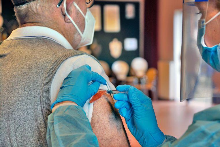 Een man wordt ingeent tegen het griepvirus. Ouderen laten zich normaal gesproken meestal inenten via de huisarts, maar vanwege het coronavirus gebeurt dit nu vaak in dorpshuizen en sporthallen. Beeld HH, ANP