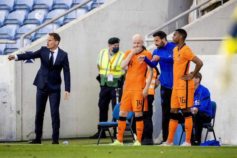 Frank de Boer probeert zijn ploeg goed neer te zetten, terwijl invallers Davy Klaassen en Ryan Gravenberch van assistent-trainer Ruud van Nistelrooij de laatste aanwijzingen krijgen.  Beeld ANP