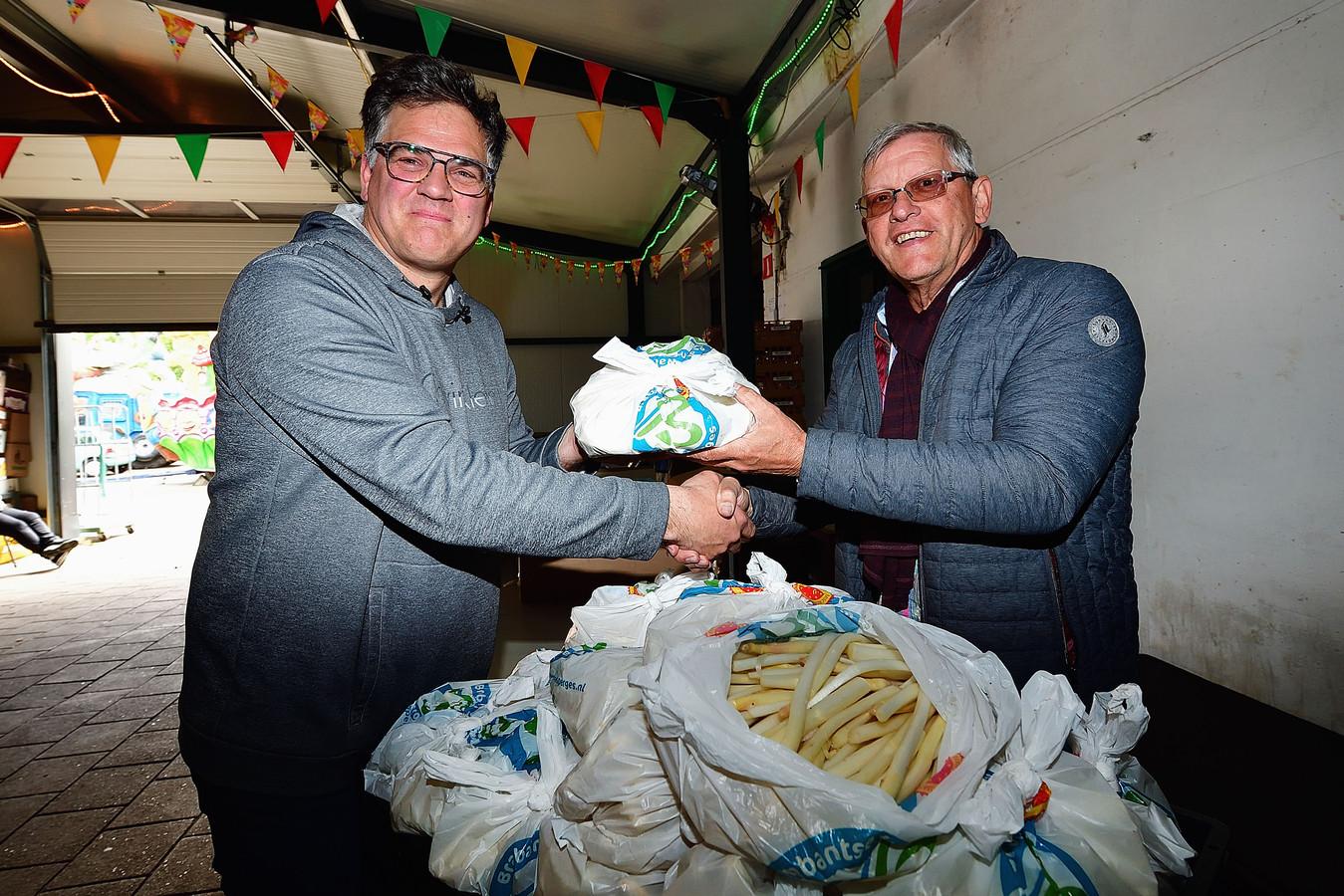 Corné Ooms (links) schenkt met Telersvereniging Brabantse Wal Asperges in totaal bijna 500 kilo geschilde asperges aan zes voedselbanken in West-Brabant. Hier overhandigt hij een lading aan Leo den Heijer van uitgiftepunt Calfven bij Ossendrecht.