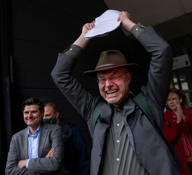Milieudefensie-directeur Donald Pols staat juichend met de uitspraak in zijn handen. Hij wil snel in gesprek met andere grote CO2-vervuilers.  Beeld AP
