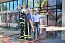 Kees van Opstal, eigenaar van Fire-Up, laat zich bijpraten door de brandweer