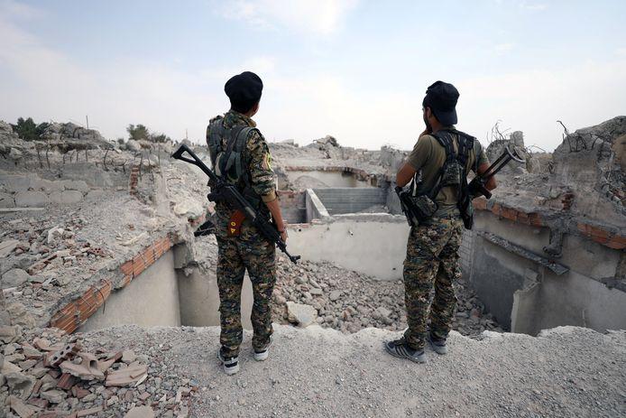 Twee militieleden bij een verwoest gebouw in Raqqa.