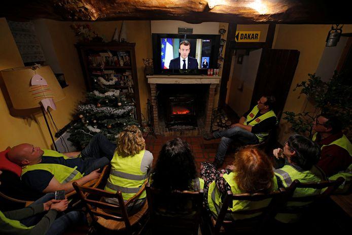 Demonstranten in gele hesjes kijken belangstellend naar de televisietoespraak van de Franse president Emmanuel Macron.