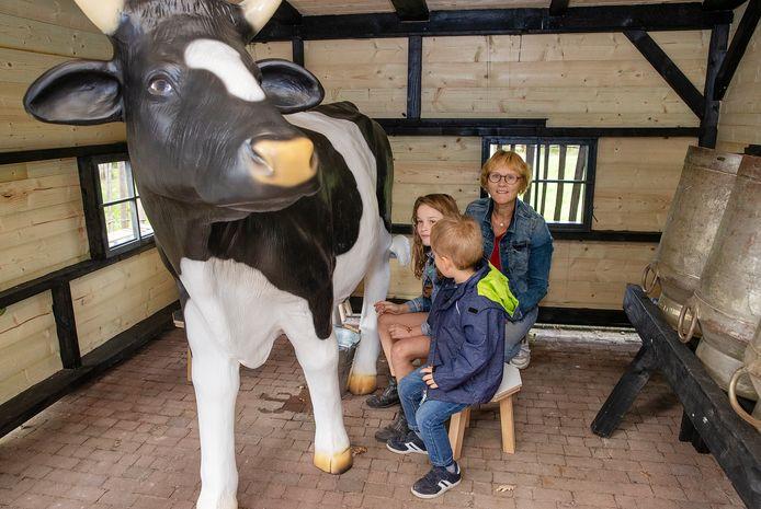 Corrie van de Ven en haar kleinkinderen bij de nieuwe oefenmelkkoe Klaartje 7.