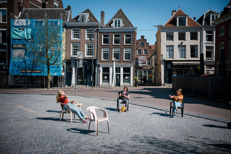 Drie vrouwen zitten op gepaste afstand van elkaar in drie stoelen op de Neude in Utrecht. Beeld Hollandse Hoogte / Erik van 't Woud