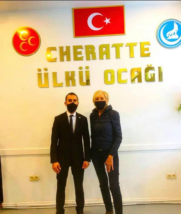 La bourgmestre de Visé posant devant le logo des Loups Gris et celui du Parti d'action nationaliste (MHP).