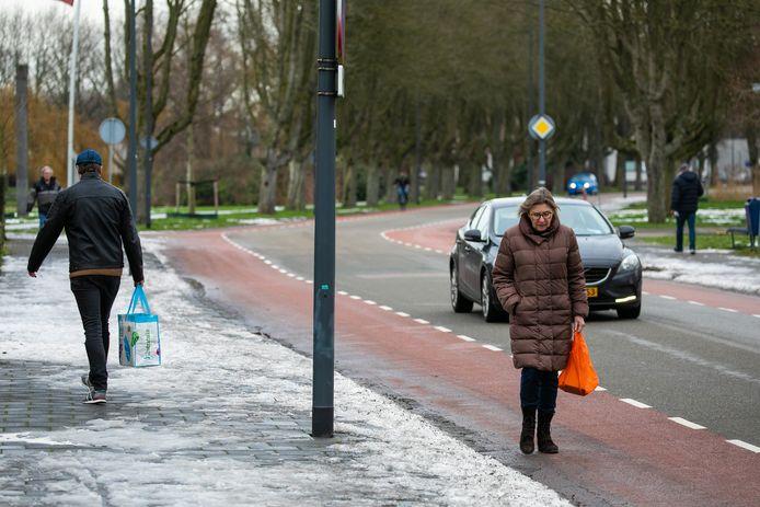 Een voetganger loopt op straat omdat de stoep nat en glad is aan de Zuiderparkweg in Den Bosch. De ander durft het wel aan.