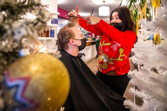 Jennifer Remrev, mede-eigenaresse van kapper Jam Hair & Make-Up, zet de schaar in het lange haar van Nick Geers.