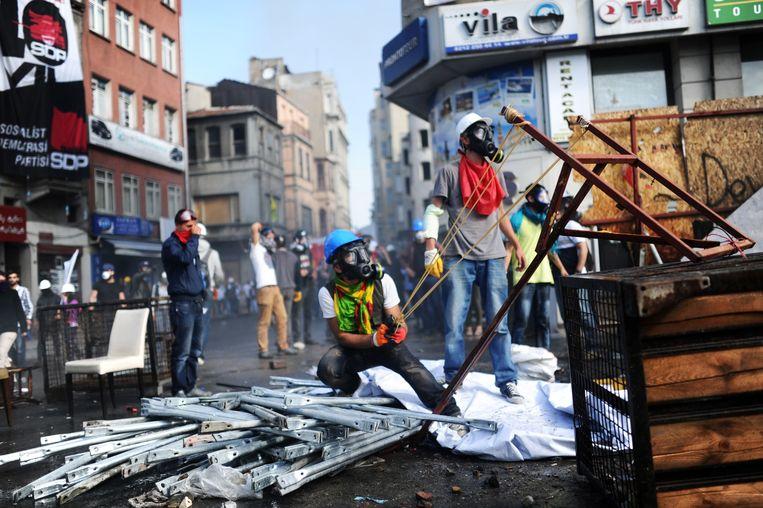 Een demonstrant op het Taksimplein in Istanbul brengt zijn katapult in stelling.  Beeld AFP