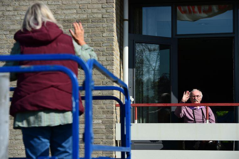 Ouderen van verpleeghuis en verzorgingshuis Van Neynsel in Den Bosch worden verrast door bezoek. Voor een dag kan gebruik worden gemaakt van een hoogwerker.  Beeld Marcel van den Bergh/de Volklskrant