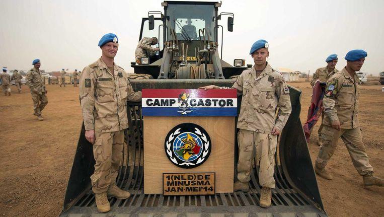 Nederlandse militairen met het wapen van kamp Castor op een shovel. Het tijdelijke legerkamp in de stad Gao werd vorige week officieel overgedragen aan de Nederlandse hoofdmacht Beeld anp