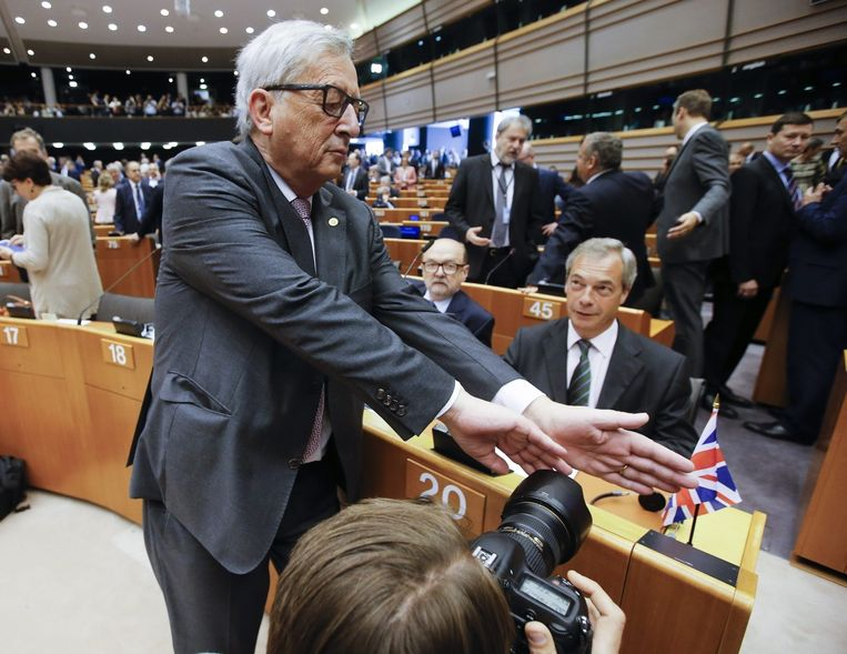 President van de Europese Commissie Jean-Claude Juncker tracht in het Europese Parlement Brexiteer Nigel Farage buiten beeld van de pers te houden. Beeld epa