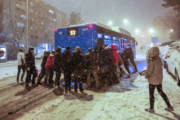 Mensen proberen een vastzittende bus te duwen in Madrid. Beeld EPA