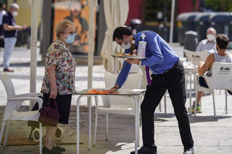 Een ober maakt een tafeltje schoon aan een plein in Madrid.  Beeld Bloomberg via Getty Images