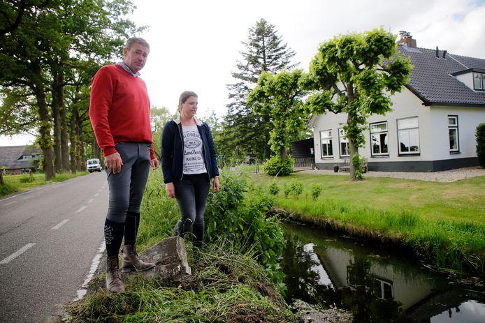 Gerd en Patricia van Delden op de plek voor hun huis waar de auto te water raakte.