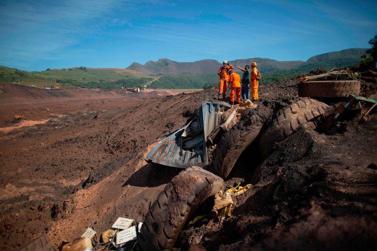 Reddingwerkers kijken uit over de moddervlakte die door de dambreuk in Brazilië werd veroorzaakt. Beeld AFP
