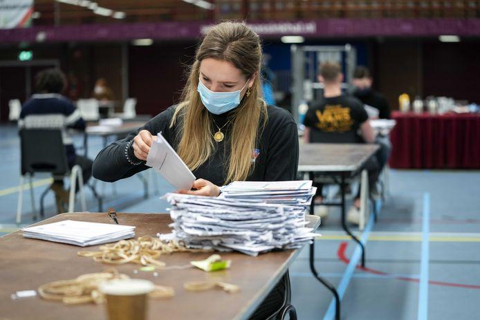 Briefstemmen worden geopend en de stemmen worden in de stembussen gegooid, hier in Nijmegen.