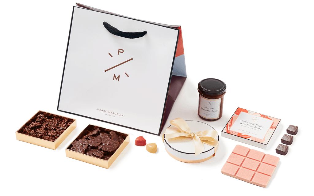 La boîte Cube Fêtes des Mères (59 euros)est composée:  • 1 tablette blanc Framboise • 1 boite ronde de 8 cœurs • 1 confiture rhubarbe-fraise • 1 Rocher Lait • 1 Croustillant noir • 1 Guimauve Vanille