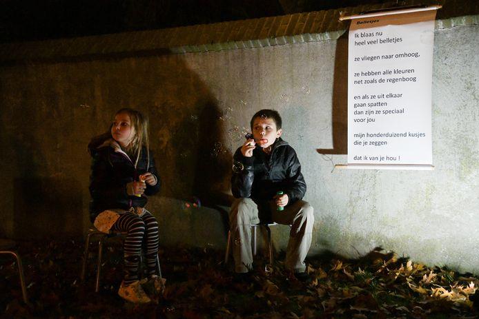 Kinderen blazen bellen bij de gedenkavond Verbonden door Licht in Druten.