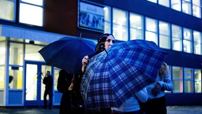 Ouders en leerlingen van de islamitische scholengemeenschap Ibn Ghaldoun verlaten een informatiebijeenkomst op een filiaal aan het Afrikaanderplein. Daar hoorden zij over de toekomst van de school, nadat bekend werd dat staatssecretaris Sander Dekker van Onderwijs de bekostiging per 1 november stopzet.