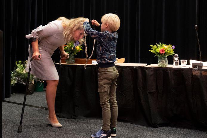 Zoon Pieter (7) hangt de ambtsketting om bij zijn moeder Marleen Sanderse.