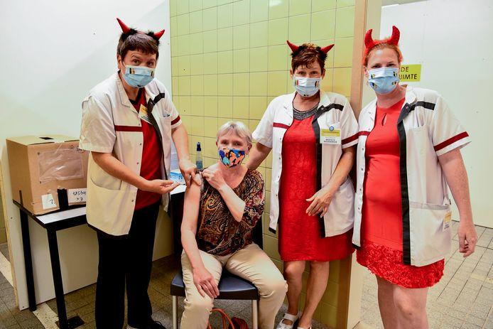 Christel krijgt een vaccin van duivelse vrijwilligsters Mieke, Roos en Nathalie.