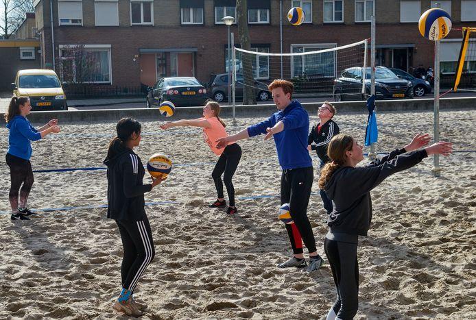 Het jeugdteam van volleybalvereniging Saturnus te Uden traint buiten. Trainer Bram Ligthart die uitleg geeft.