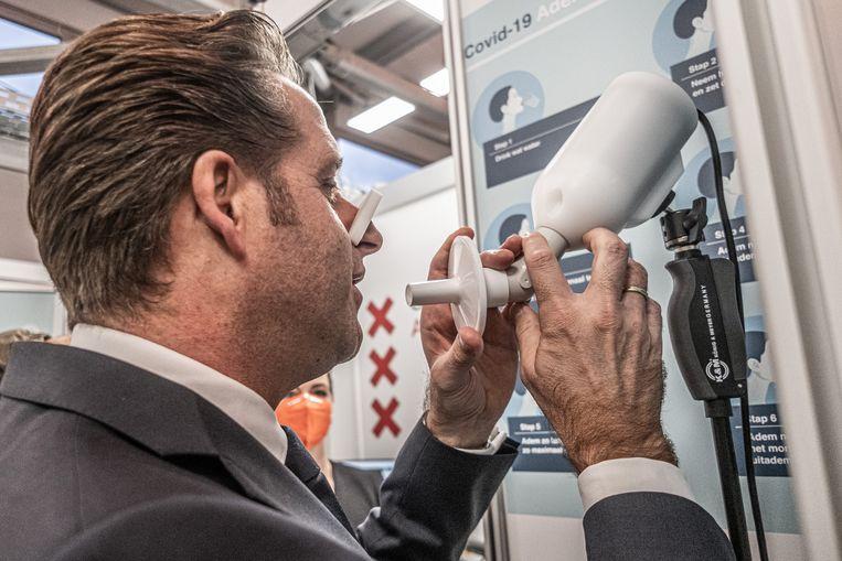 Minister van Volksgezondheid Hugo de Jonge bezoekt in Amsterdam een GGD-teststraat om de blaastest SpiroNose te bewonderen.  Beeld Joris van Gennip