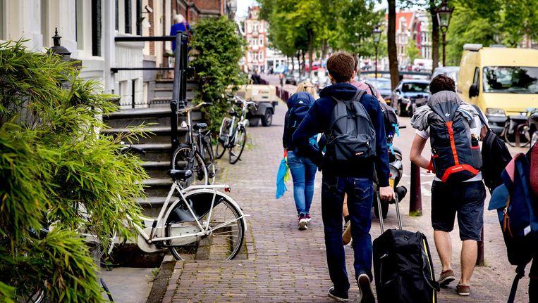 Toeristen met rolkoffers op de grachten in Amsterdam. Beeld ANP