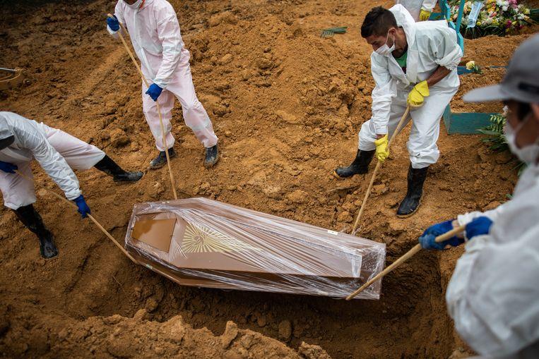 Gehuld in beschermende kleiding begraven Brazilianen een covidslachtoffer. In het land sterven nu dagelijks bijna tweeduizend mensen als gevolg van de ziekte. Beeld EPA