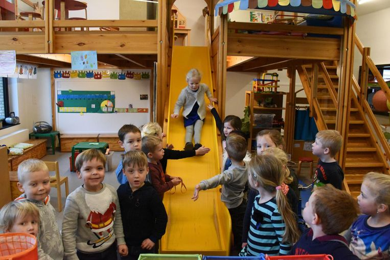 Deze klas telt zowaar een mezzanine, bereikbaar via een trap. Naar beneden gaan, doen de kleuters langs een knalgele glijbaan.