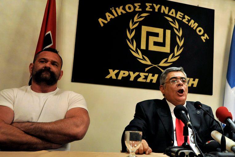 Nikos Michaloliakos (rechts) van de Griekse neonazistische partij Gouden Dageraad, zondagavond na het sluiten van de stembussen. Beeld EPA