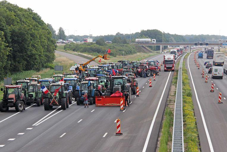 Boeren staan vrijdag met trekkers op de A1 tussen Hengelo en Apeldoorn. Beeld ANP